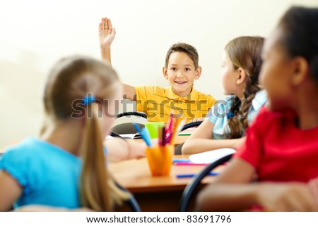 Image of smart pupil raising arm during the lesson