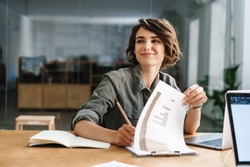 Image of smiling beautiful woman writing down notes while sitting at table in office