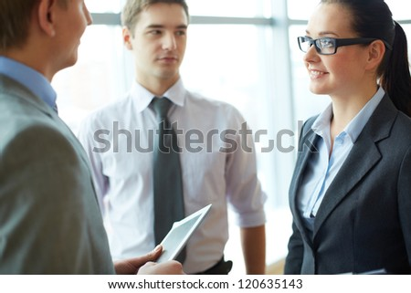 Image of smiling businesswoman listening to male employee