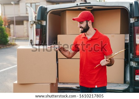 Image of smiling delivery man in red uniform writing while standing with parcel boxes near car outdoors