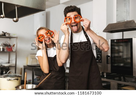 Image of smiling excited young friends loving couple chefs on the kitchen cooking having fun covering eyes with paprika.