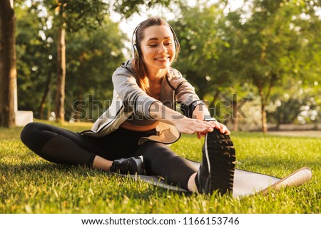 Image of smiling fitness woman 20s wearing headphones working out and stretching legs while sitting on exercise mat in green park