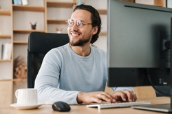 Image of smiling unshaven programmer man wearing eyeglasses working with computer in office