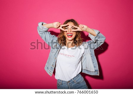 Image of smiling young woman isolated over pink background. Looking camera showing peace gesture.