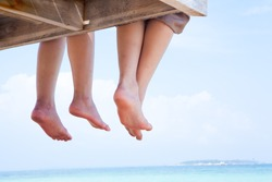 Image of soles of two people lying on sandy beach