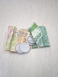 image of some money. 20,000 rupiah, 5,000 rupiah, and some 500 rupiah coins