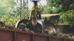 Image of special claw gripper lfrabbing and lifting metal waste on scrapyard