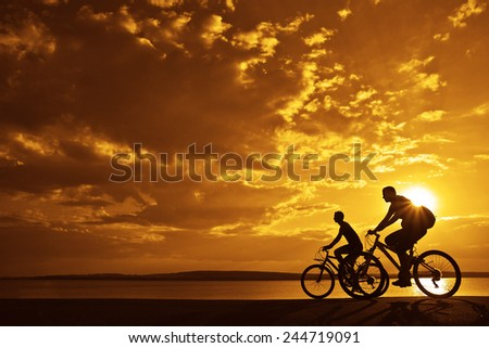 Image of sporty company friends on bicycles outdoors against sunset mountain. Silhouette of motion go of two 2 cyclist along shoreline coast Reflection sun on water Copy Space for inscription #244719091