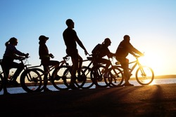 Image of sporty company friends on bicycles outdoors against sunset. Silhouette.