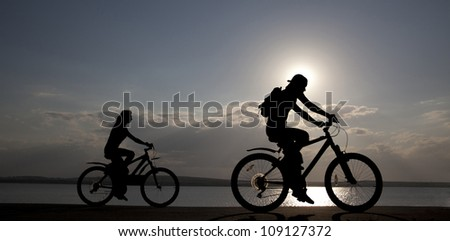 Image of sporty couple on bicycles outdoors against sunset. Silhouette. space for inscriptions