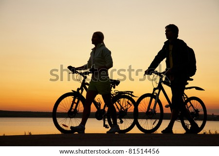 Image of sporty couple with bicycles walking  outdoors against sunset. Silhouette.