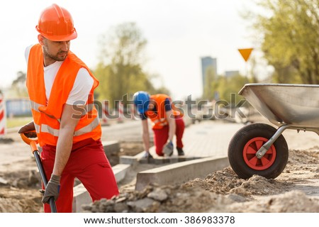 Image of strong construction worker digging the ground