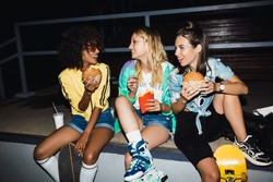 Image of stylish multiethnic girls eating fastfood and drinking soda at night outdoors