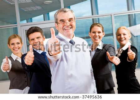 Image of successful business team keeping their thumbs up with senior leader in front smiling at camera