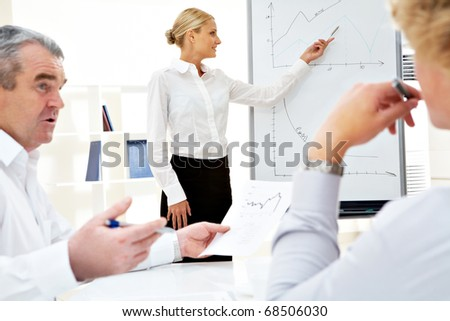 Image of successful businesswoman standing by whiteboard while her colleagues listening to her