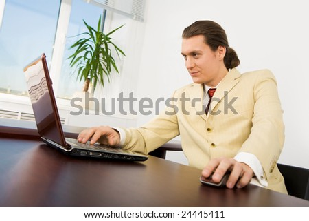 Image of successful employer working in the Internet in office