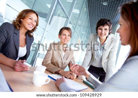 Image of successful females listening to colleague at meeting