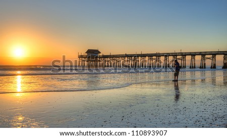 image of sunrise at cocoa beach with silhouette of walker