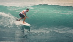 Image of Surfer on Blue Ocean Wave in Bali, Indonesia. Surfer riding in tube. Short surfboard. Deep adventure