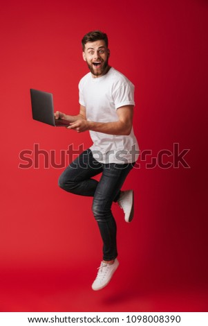 Image of surprised young man jumping isolated over red wall background using laptop computer. Looking camera. #1098008390