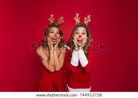 Image of surprised young women friends wearing christmas deer costumes standing isolated over burgundy background wall. Looking at camera. #744953728