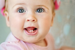 Image of sweet and cute baby girl in pink, closeup portrait of cute 8 month-old smiling girl,  toddler.