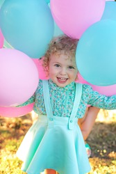 Image of  sweet and funny baby girl with balloons, closeup portrait of child, cute toddler with amazed smiling face. Two years old.