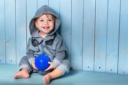 Image of  sweet baby boy, closeup portrait of child, cute toddler with blue eyes.small boy sits, smiles and keeps the ball.