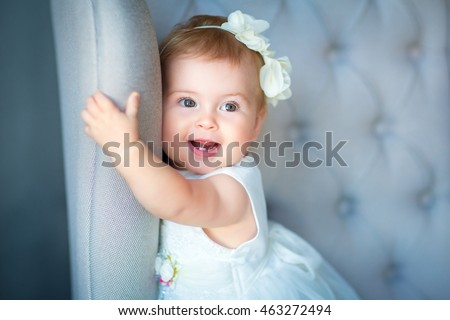 Image of sweet baby girl in a wreath, closeup portrait of cute 8 month-old smiling girl,  toddler.