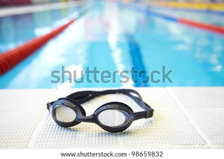 Image of swimming pool and goggles. Nobody