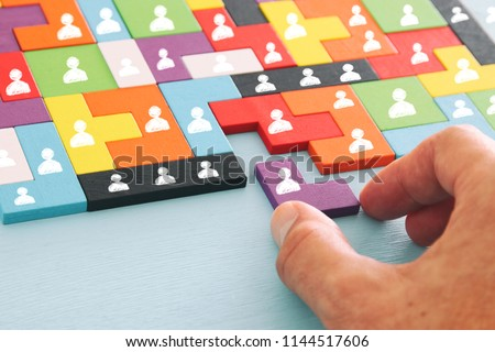 image of tangram puzzle blocks with people icons over wooden table ,human resources and management concept #1144517606