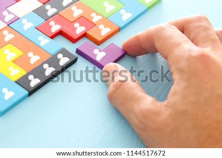 image of tangram puzzle blocks with people icons over wooden table ,human resources and management concept #1144517672