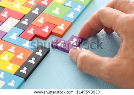 image of tangram puzzle blocks with people icons over wooden table ,human resources and management concept #1149593039