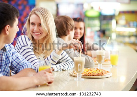 Image of teenage couple interacting in cafe
