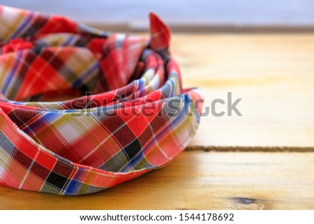 """Image of """"tengkolok"""" know as destar, traditional Malay male headgear on wooden surface. Made from cloth folded and tied in particular style. Worn in ceremony. Selective focus only."""
