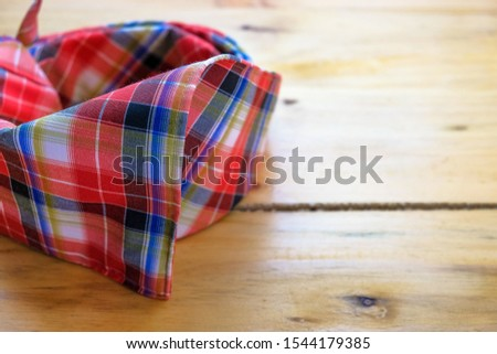 """Image of """"tengkolok"""" known as destar, traditional Malay male headgear on wooden surface. Made from cloth folded and tied in particular style. Worn in ceremony. Selective focus only."""