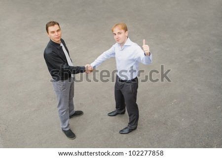 Image of the business partners concluding a bargain. Focus is made on top of the gray background of the empty street.