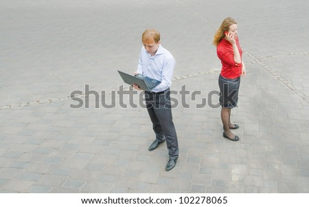 Image of the business partners using communication and standing on the street. They have absolutely thoughtful and purposeful face.