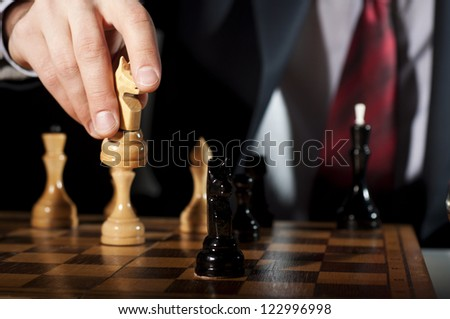 image of the businessman in a business suit plays chess