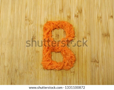 "Image of the handmade vegetables letter ""B"" made of grated carrot isolated on the wodden chopping board. Perfect font for making vegan, vegetarian texts. All alphabet letters in my portfolio."