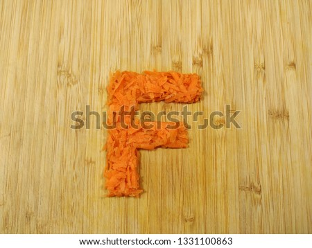 "Image of the handmade vegetables letter ""F"" made of grated carrot isolated on the wodden chopping board. Perfect font for making vegan, vegetarian texts. All alphabet letters in my portfolio."