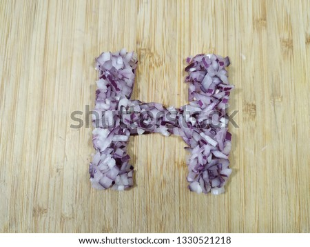 "Image of the handmade vegetables letter ""H"" made of chopped  purple onion isolated on the wodden chopping board. Perfect font for making vegan, vegetarian texts. All alphabet letters in my portfolio."