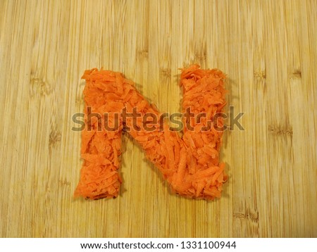 "Image of the handmade vegetables letter ""N"" made of grated carrot isolated on the wodden chopping board. Perfect font for making vegan, vegetarian texts. All alphabet letters in my portfolio."