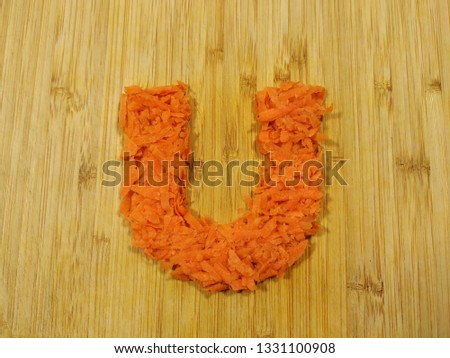 "Image of the handmade vegetables letter ""U"" made of grated carrot isolated on the wodden chopping board. Perfect font for making vegan, vegetarian texts. All alphabet letters in my portfolio."