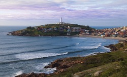 Image of the Santa Marta Lighthouse in Santa Catarina in Brazil, photo at dawn and from Morro do Céu towards the Santa Marta Lighthouse, showing the Lighthouse, the houses and the beach.