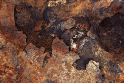 Image of the surface of a rock decomposing by seawater erosion, with earthy colors, brown, yellow and gray. Unique textures of cracks, holes, crevices and layers in rougher state. Top view.