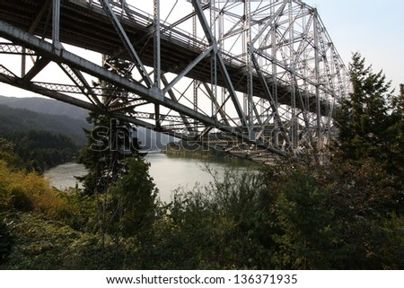 image of the vintage Metal bridge ( Bridge of the gods) over the Columbia River Gorge at the border of Oregon and the state of Washington. This image brings out the vintage feel of the bridge.