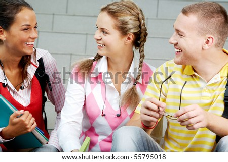 Image of three attractive students chatting before lesson