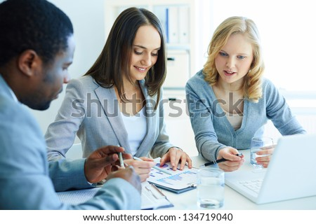 Image of three business partners discussing documents at meeting