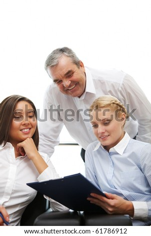 Image of three business people looking at document and smiling